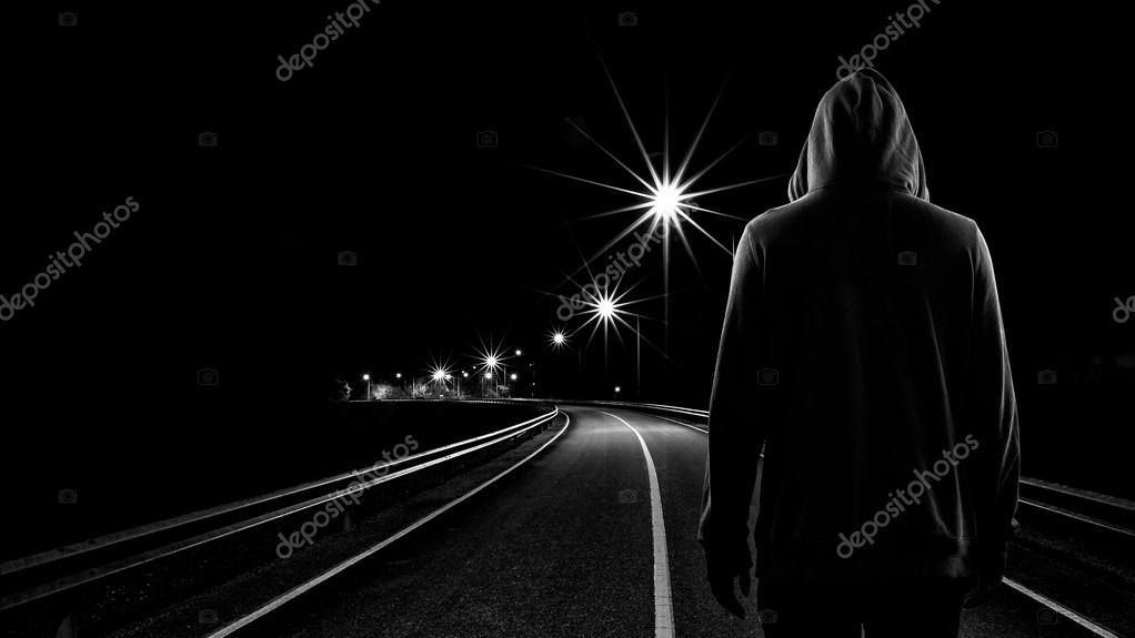 Teenager boy standing alone in the street at night