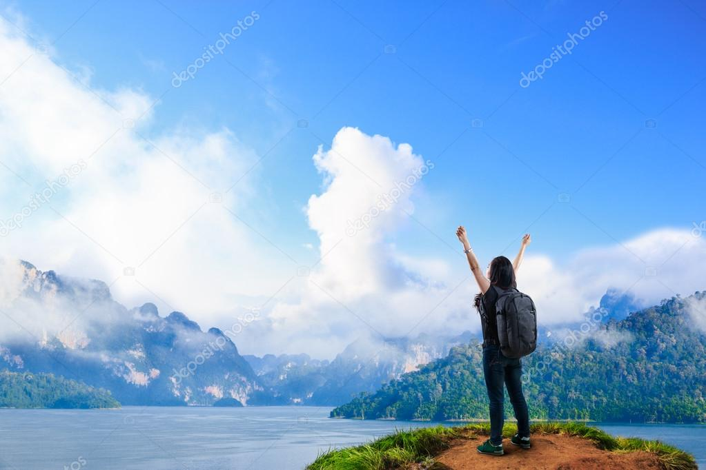 Young happy girl with backpack standing near big river with rais
