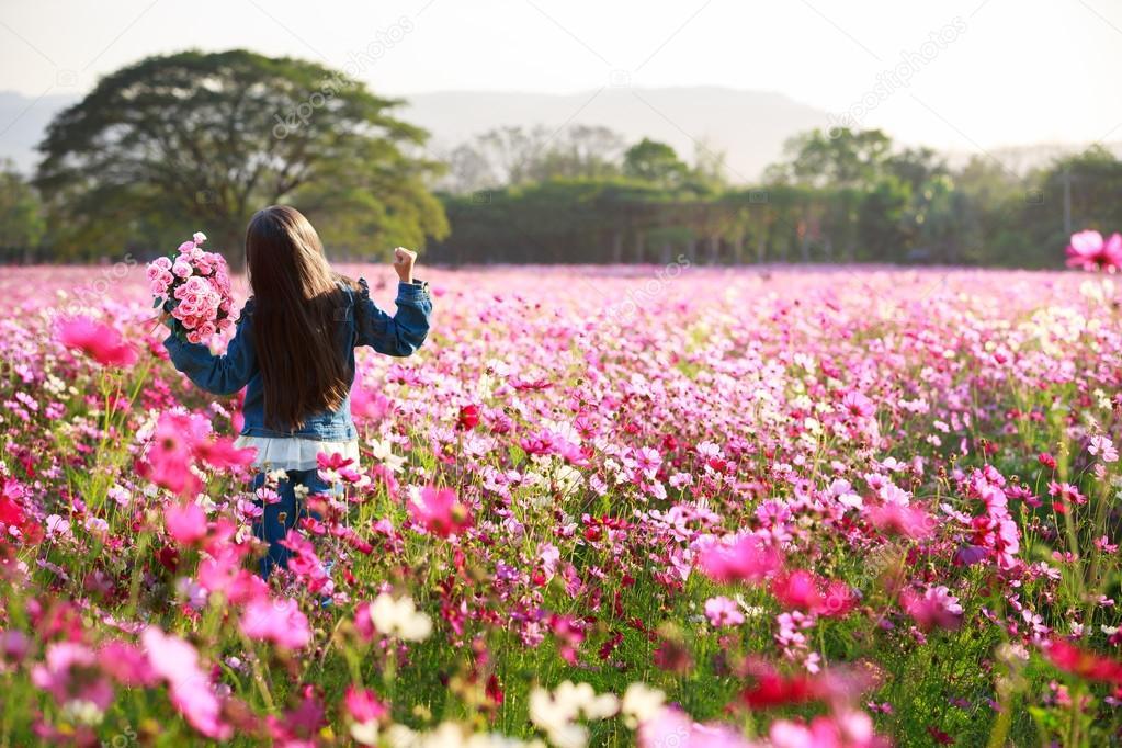 Little asian girl standing in flower fields