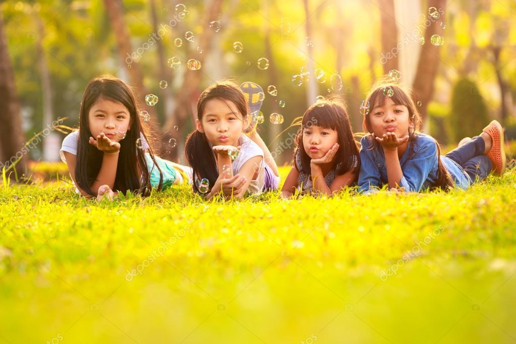 Crianças Se Divertindo No Parque: Bonitos Crianças Se Divertindo De Bolha No Gramado Verde