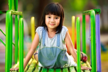 Little asian girl sitting on slide at playground