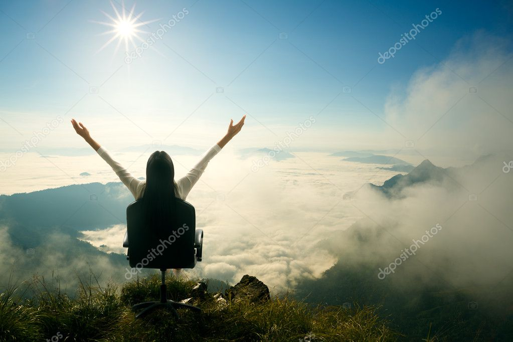 Young woman sits on a chair and open her arms at the top of the