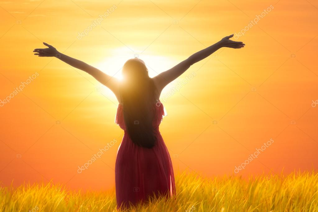 Young asian woman standing open her arms under the sunrise