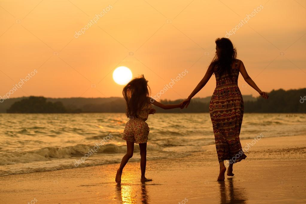 Mother and daughter running on the beach