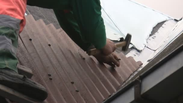 muž na žebříčku zatloukání střešním plášti