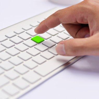 Hand pushing green keyboard button