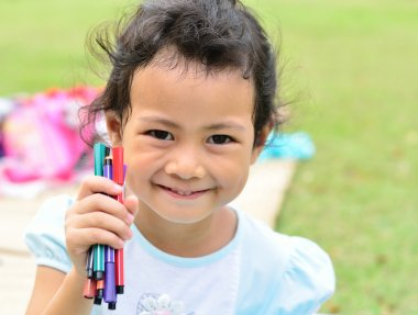 Going back to school : Little girl holding color pens