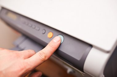 Office life, hand pressing start button on fax, copy machine