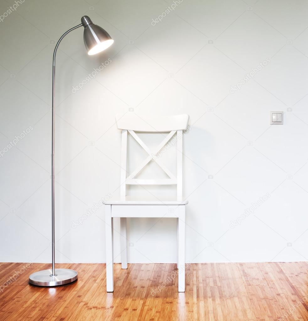 Wooden Chair with floor lamp to face a blank white wall