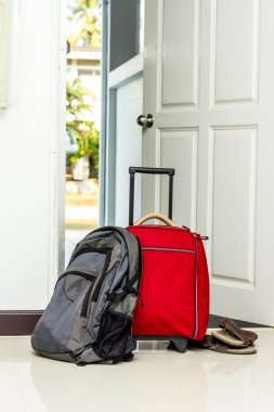 red travel bag , backpack and shoes