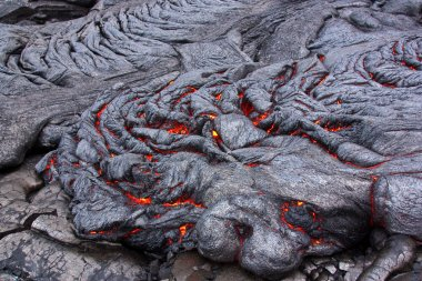 Lava flow cracks glowing in red