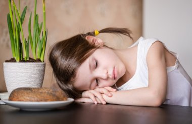 Adorable preschooler girl sleeping in the kitchen