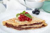 Fotografie Palatschinken mit Marmelade und Nutella in den Topf auf den Tisch