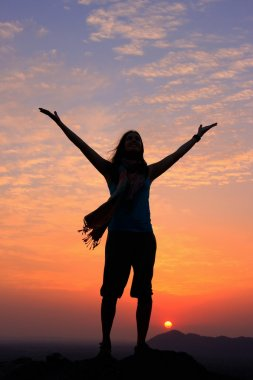 Sillouetted woman with her arms up at sunset on top of the hill,