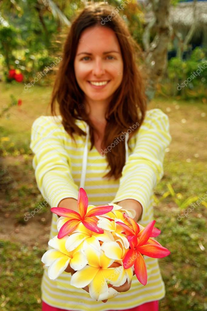 Young woman holding white and pink plumeria flowers in her hands