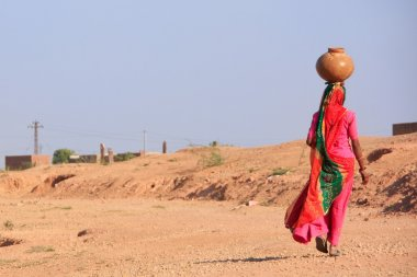 Local woman carrying jar with water on her head, Khichan village