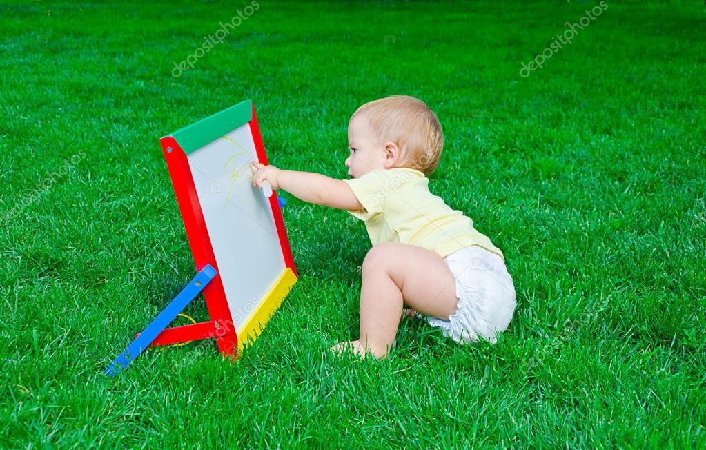 А beautiful little boy draws sitting on a lawn