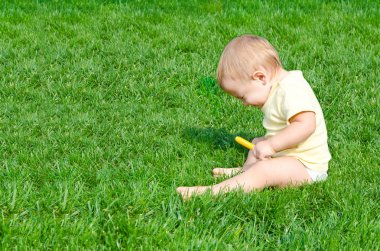 А pretty little boy sneezes sitting on a grass