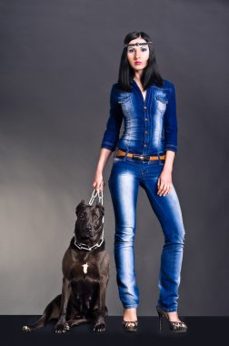 Beautiful young woman in jeans clothes standing next to a dog