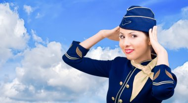 Smiling stewardess in uniform on a background sky
