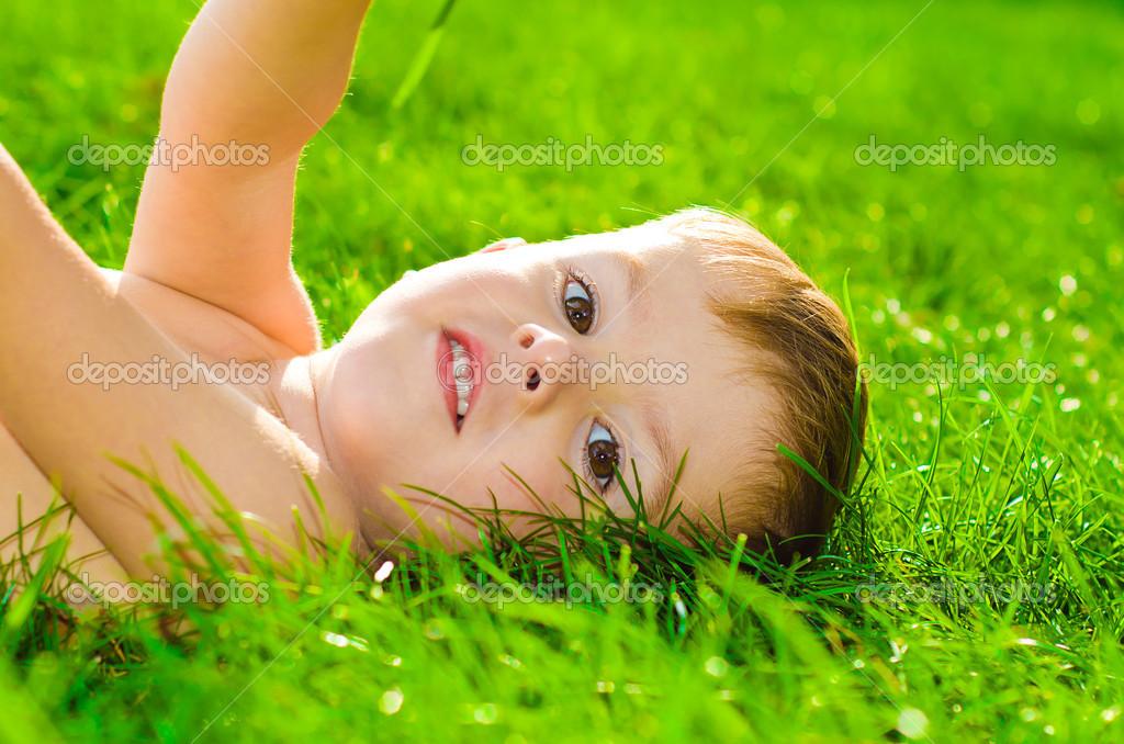 Portrait of little beautiful boy lying on the grass