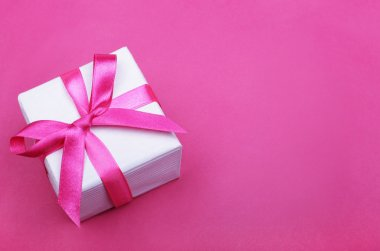 Gift box with pink ribbon on pink background