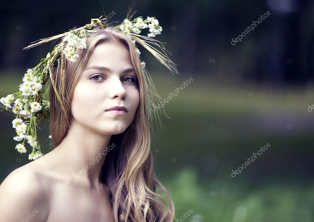 Portrait of the girl in a wreath from camomiles and ears
