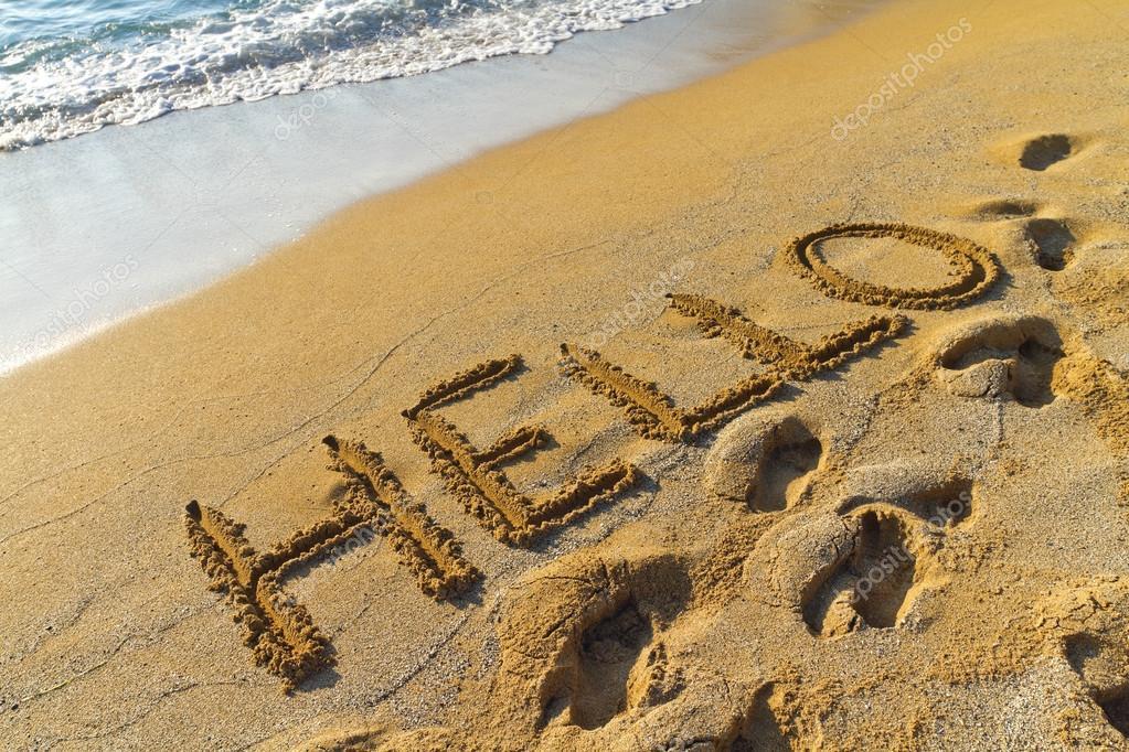 hello greeting written in a golden sandy beach