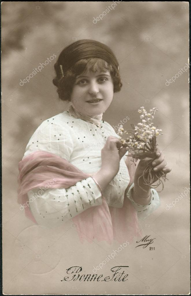 Old Swiss postcard 1917. Shows a girl with flowers. The inscription in French: Happy Birthday