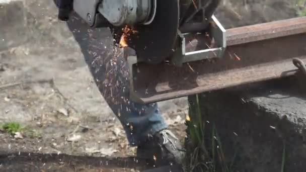 Worker cuts the rail angle grinder