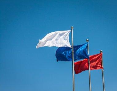 Three flags against blue sky.