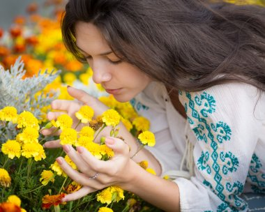 Young woman smelling flowers.