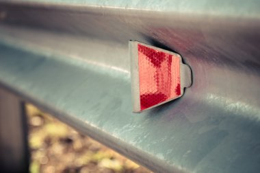 Red reflector on road.