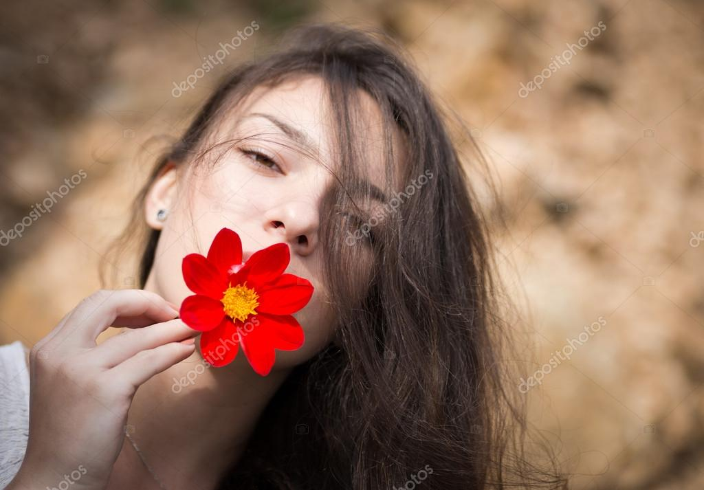 Portrait of young woman with flower.