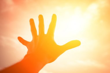 Hand reaching to sunshine sky.