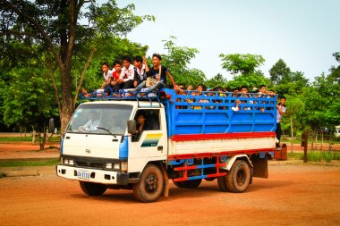 Students getting on a truck used as school bus