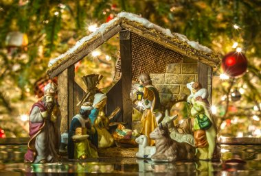 Old handmade nativity scene in front of a christmas tree