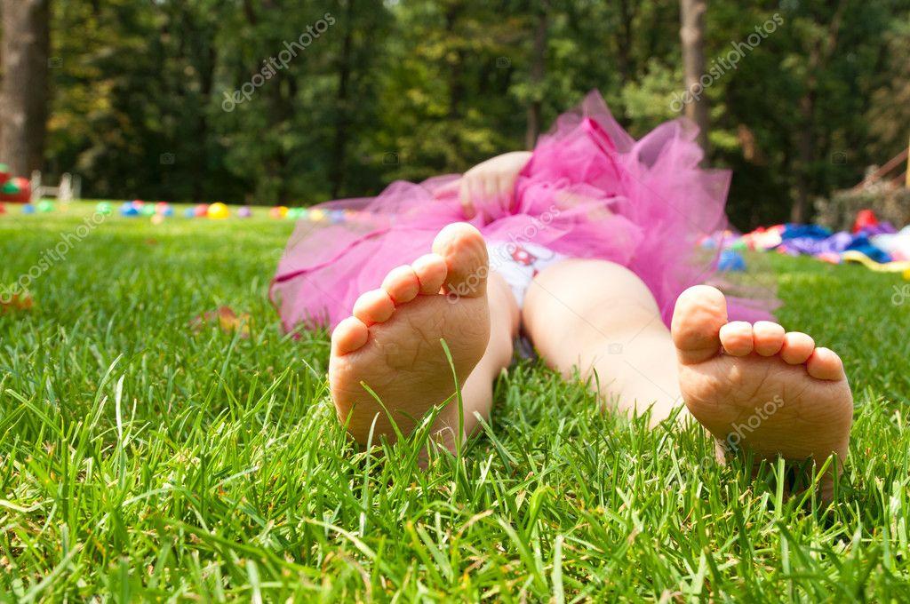 happy little girl lying on green grass