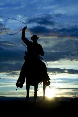 Cowboy on horse facing roping