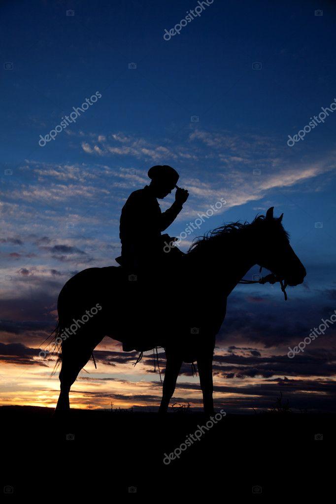 Cowboy holding hat horse sunset