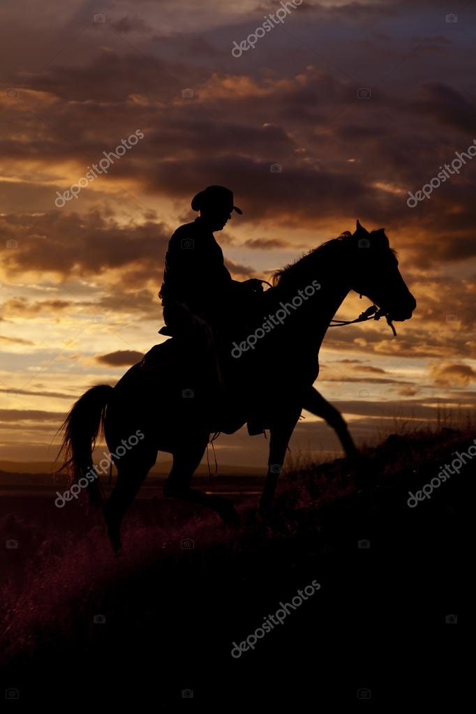 Cowboy riding horse up hill