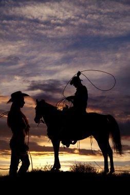 Cowboy on horse swinging rope