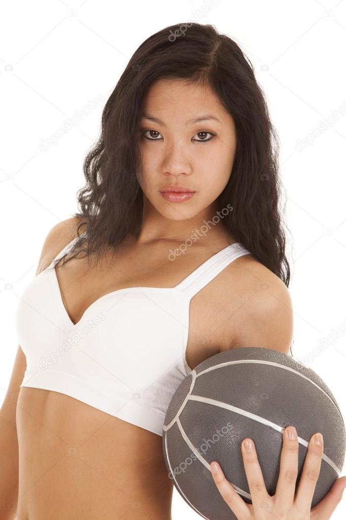 7100bbafef55b A woman holding on to a weighted medicine ball with a serious expression.