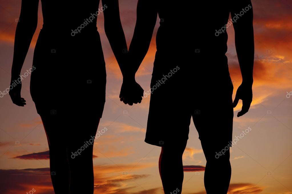 a silhouette of a man and woman holding hands walking photo by alanpoulson