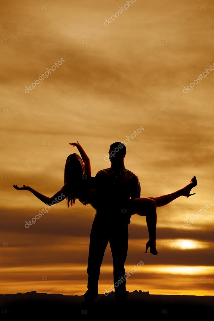 silhouette of man holding woman with arms out