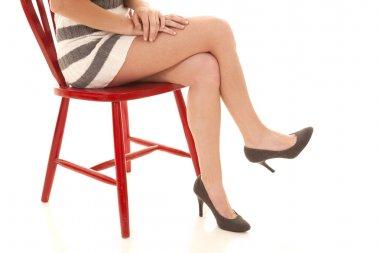 Woman legs skirt red chair