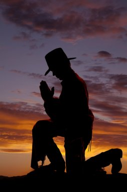 Silhouete cowboy kneel head down.