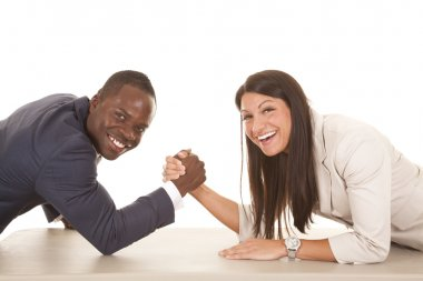 business man and woman arm wrestle laugh looking