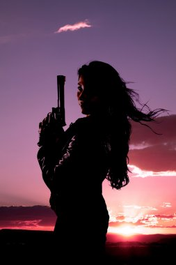 Woman gun hair blowing sunset