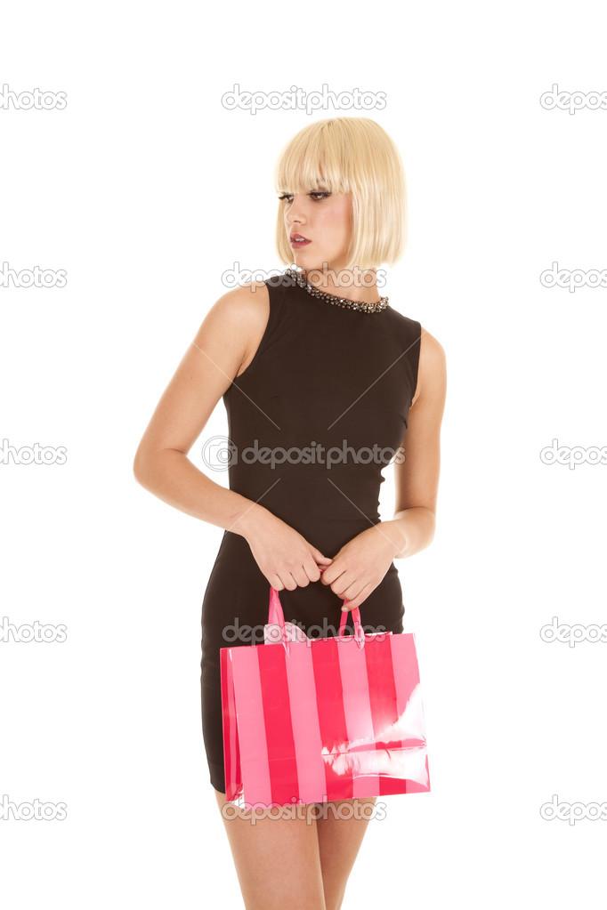 Frau schwarzes Kleid rosa Tasche Stand Blick Seite — Stockfoto ...